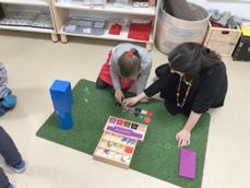 Pédagogie Montessori - L'éducatrice avec une fille, materiel Montessori